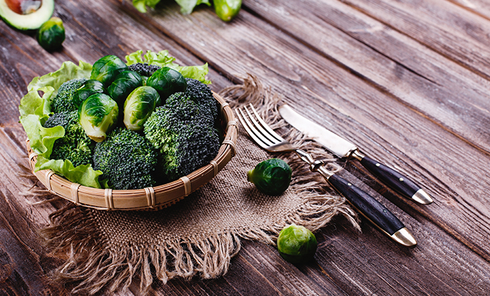 fresh healthy food wooden bowl with broccoli Brussel sprouts olive oil green pepper