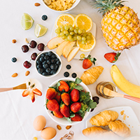 Healthy fresh fruits with egg and croissant on white background