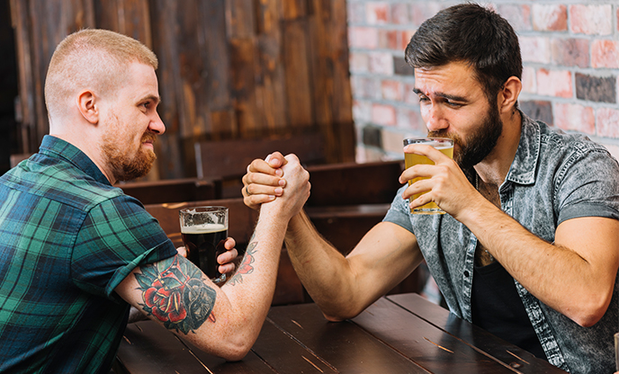 man drinking beer while arm wrestling with his friend