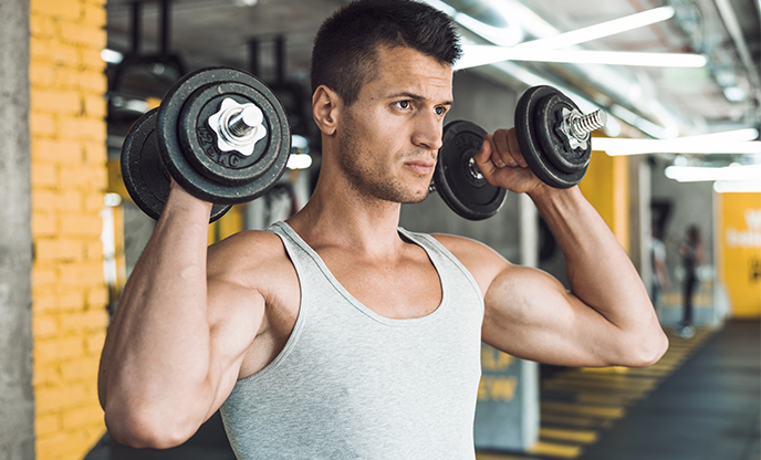 Young man doing exercise with dumbbells strengthening his shoulder