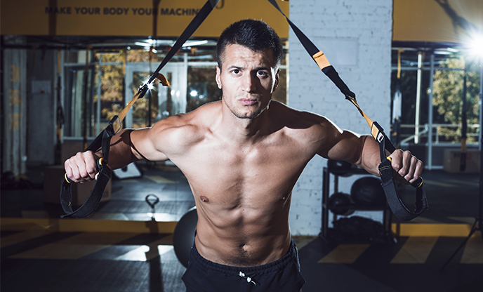 muscular-man-exercising-with-fitness-strap-gym