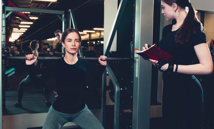 female-instructor-evaluating-fitness-performance-young-woman-exercising-gym
