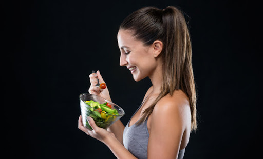 beautiful-young-woman-eating-salad-black-background-Healthiest Self in 10 minutes