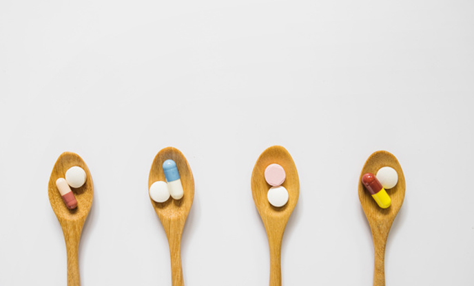 overhead-view-wooden-spoons-with-body-boost-pills-isolated-white-background
