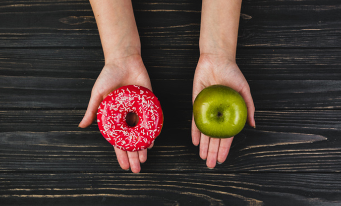 crop-hands-holding-donut-apple-Calorie-Myth